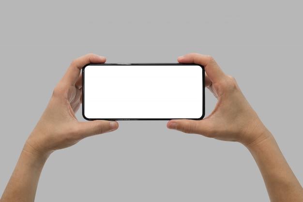 Mano que sostiene el teléfono móvil negro con pantalla en blanco aislado en gris