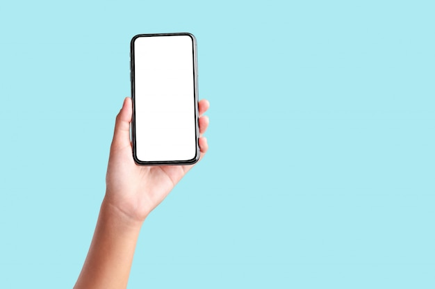 Mano que sostiene el teléfono móvil de la pantalla en blanco aislado en la pared azul