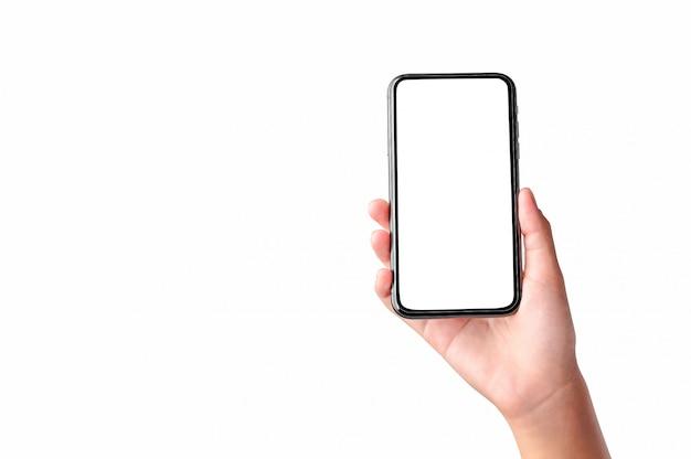 Mano que sostiene el teléfono móvil de la pantalla en blanco aislado en la pared blanca