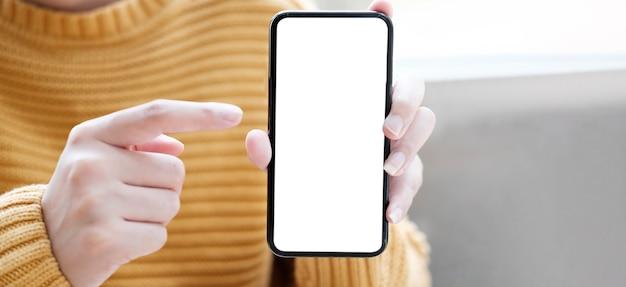 Mano que sostiene el teléfono móvil con pantalla en blanco