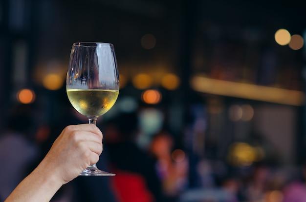 Mano que sostiene un vaso de vino blanco con luz de colores bokeh en restaurante.