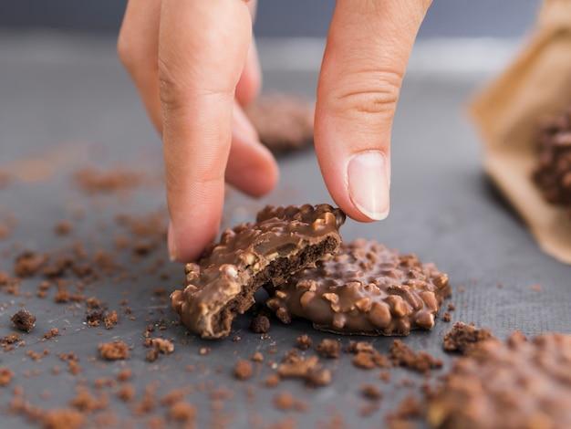 Mano que toma la galleta de chocolate pellizcada de la mesa