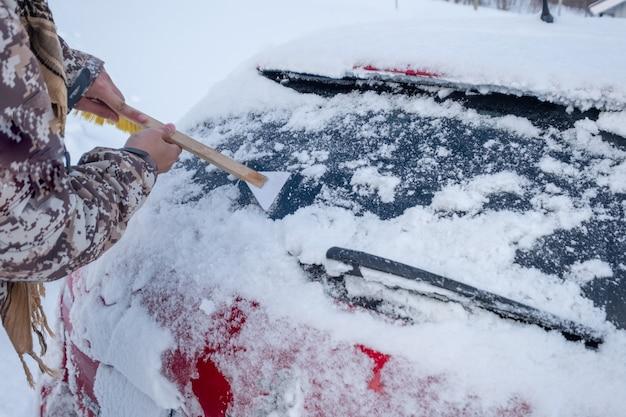 Mano que usa la tela para raspar la nieve en el parabrisas trasero del automóvil
