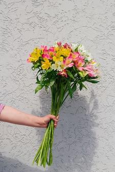 Mano con ramo de flores de alstroemeria contra un muro de hormigón en bruto