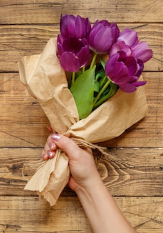 Mano con ramo de tulipanes morados en papel artesanal sobre mesa de madera de cerca