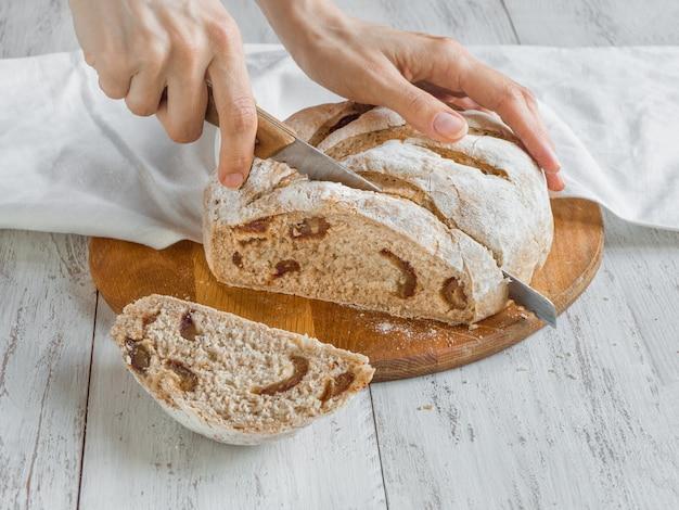 Mano rebana pan fresco con fechas.