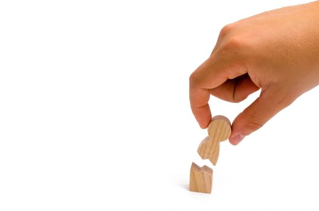 La mano recoge la figura humana rota. asistencia psicológica a víctimas de violencia.