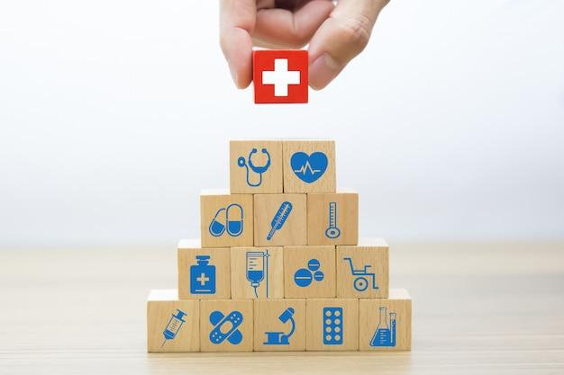 Mano recogiendo bloques de madera apilamiento con icono médico y de salud.