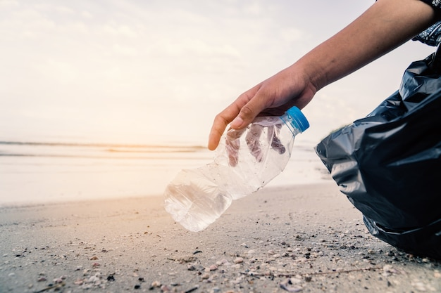 Mano recogiendo botellas de plástico de limpieza en la playa, concepto voluntario.