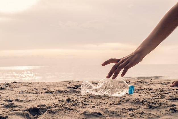 Mano recogiendo botellas de plástico en la playa, voluntario para salvar el medio ambiente