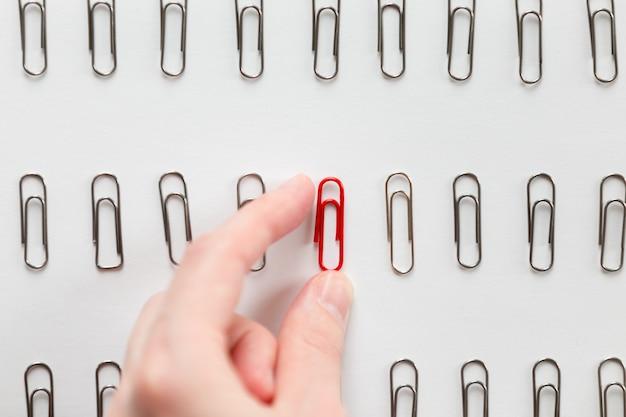 Mano recogiendo entre los clips de papel de metal uno rojo, diferente de otros