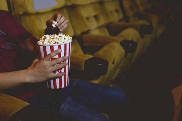 Mano recogiendo palomitas de maíz del cubo de palomitas de maíz en un cine.