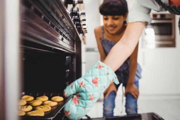 Mano recortada de mujer colocando galletas en el horno