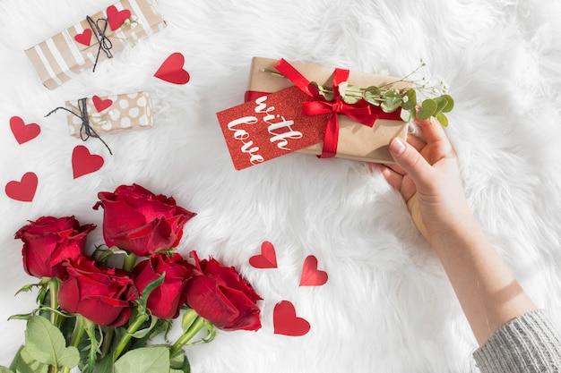 Mano con regalo con etiqueta cerca de corazones de adorno y flores frescas en cobertor de lana