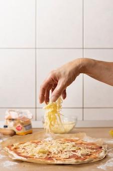 Mano rociando mozzarella sobre masa de pizza