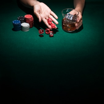 Mano rodando dados del casino mientras sostiene un vaso de whisky