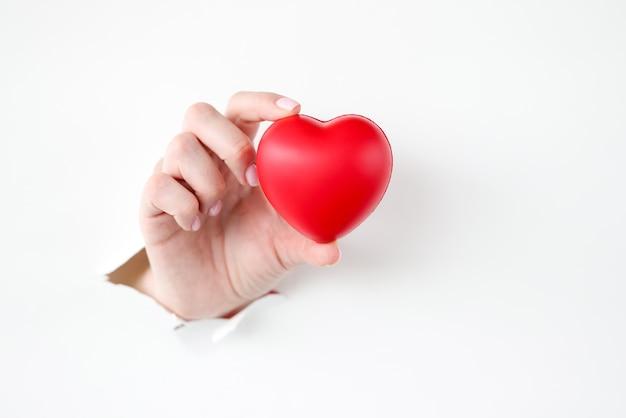 Mano sacando juguete corazón rojo de papel rasgado