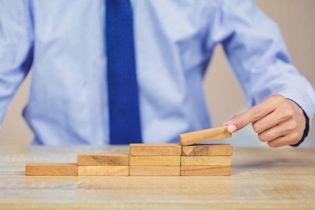 Mano sacando o colocando un bloque de madera en la torre, el plan y la estrategia en los negocios