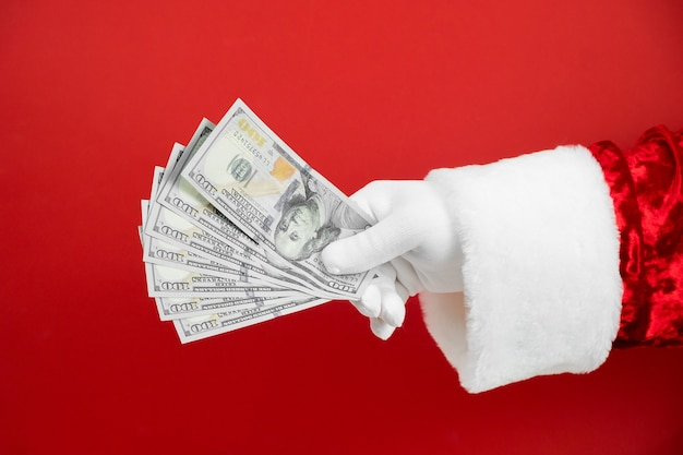 Mano de santa claus con dinero en rojo