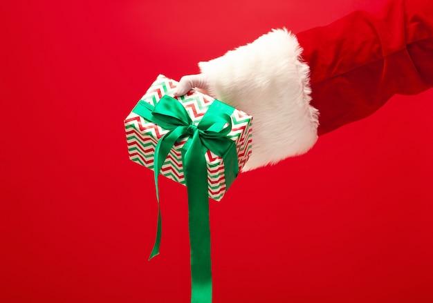 La mano de santa claus sosteniendo un regalo sobre fondo rojo. la temporada, invierno, vacaciones, celebración, concepto de regalo.