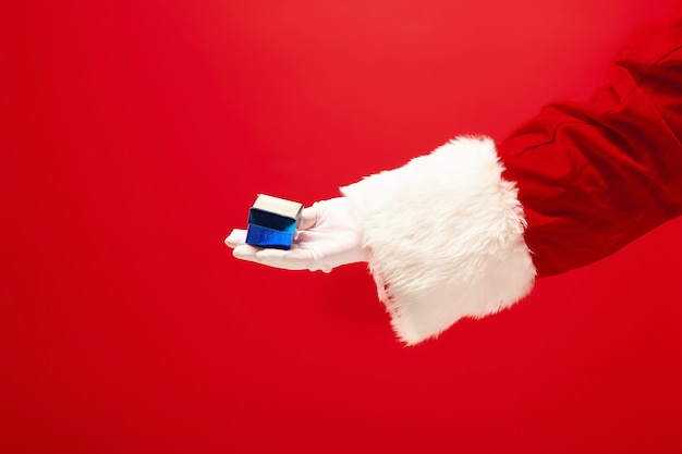 Mano de santa claus sosteniendo un regalo sobre fondo rojo. temporada, invierno, vacaciones, celebración, concepto de regalo