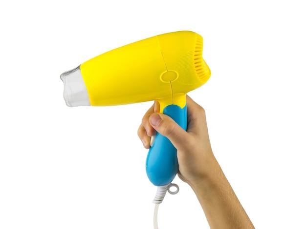Mano con secador de pelo amarillo-azul aislado sobre superficie blanca