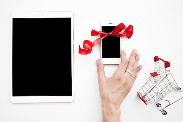 Mano de la señora en el teléfono inteligente cerca de la tableta y carrito de la compra