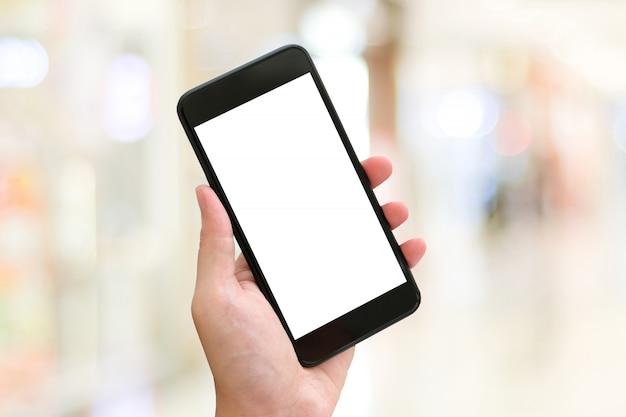 Mano con smartphone con pantalla en blanco sobre fondo claro de desenfoque bokeh