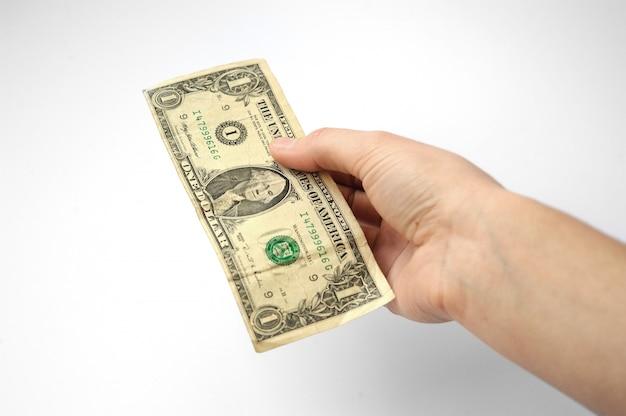 La mano sobre un fondo blanco se extiende de billetes en denominación