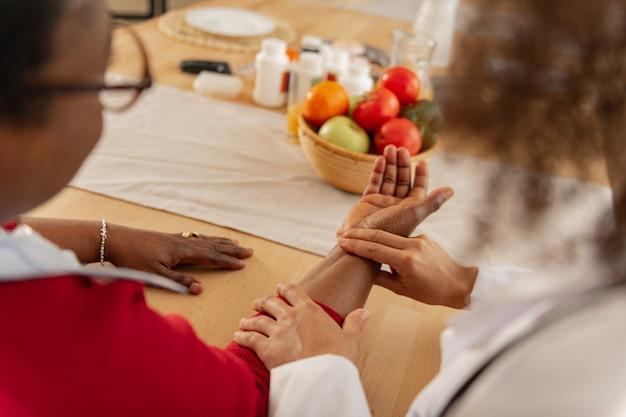 Mano sobre la mesa. mujer con gafas poniendo su mano sobre la mesa para que una enfermera profesional mida el pulso