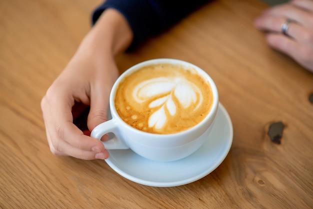 Mano sobre la mesa una taza de café