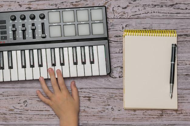 Una mano sobre un mezclador de música y un cuaderno con un bolígrafo sobre una mesa de madera