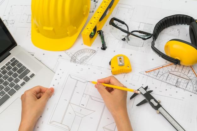 Mano sobre planes de construcción con casco amarillo y una herramienta de dibujo