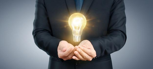 Mano de sostener bombilla iluminada, concepto de inspiración de innovación de idea