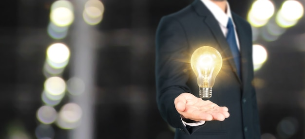 Mano de sostener bombilla iluminada, concepto de inspiración de innovación