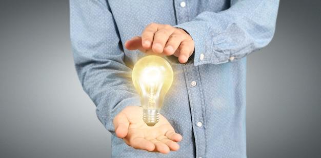 Mano de sostener bombilla iluminada, inspiración de innovación