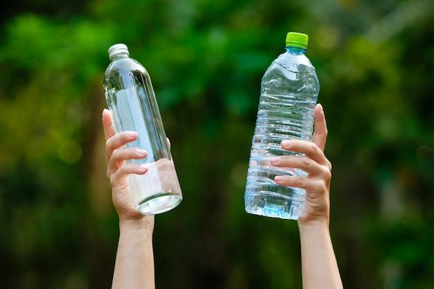 Mano sostenga agua en blanco vidrio y botella de plástico