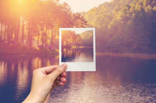 Mano sostenga la foto instantánea agua y amanecer de la charca con efecto vintage.