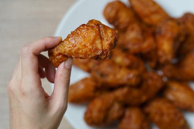 Mano sosteniendo alitas de pollo fritas picantes
