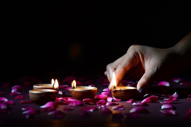 Mano sosteniendo y arreglando la linterna (diya) durante el festival de las luces de diwali