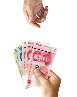 Una mano sosteniendo el billete de yuan de china para dar y una mano en blanco esperando recibirlo