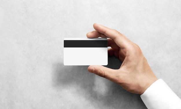 Mano sosteniendo en blanco maqueta de tarjeta de crédito en blanco banda magnética negra