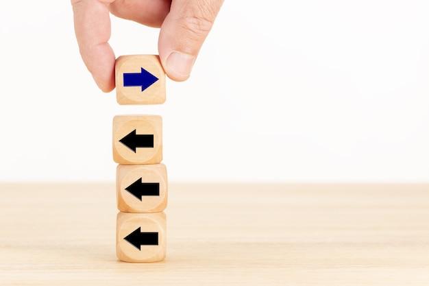 Mano sosteniendo un bloque de madera con el icono de flecha en dirección opuesta a los demás. concepto diferente al de otras personas. buscando el éxito. copia espacio