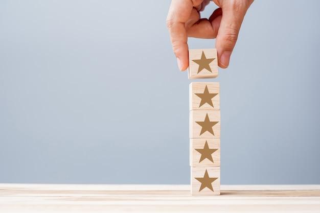 Mano sosteniendo bloques de madera con el símbolo de la estrella. opiniones de clientes, comentarios, calificación, clasificación y concepto de servicio.