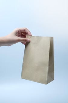 Mano sosteniendo una bolsa de papel