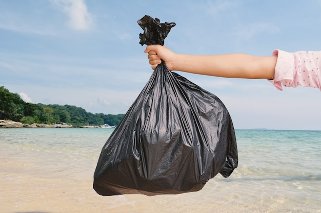 Mano sosteniendo la bolsa de plástico en la orilla del mar
