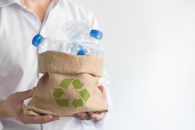 Mano sosteniendo la bolsa de saco con basura reciclar botellas de plástico, solución de calentamiento global.