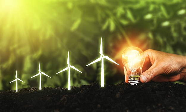 Mano sosteniendo la bombilla y aumentar el molino de viento de icono digital. ahorrando energía en la naturaleza