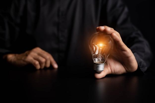 Mano sosteniendo bombillas, ideas de nuevas ideas hermosas creativas y comunicar los nuevos inventos con tecnología innovadora y creatividad.