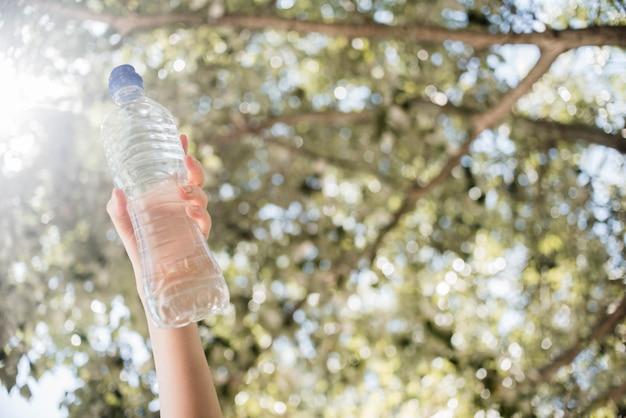 Mano sosteniendo botella de agua